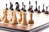 stock photo of chess piece  - Chess pieces setup before the game - black and white chess pieces standing on a chessboard