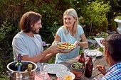 picture of gathering  - woman passing fresh healthy salad at outdoor friends dinner party gathering - JPG