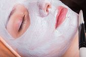 stock photo of black woman spa  - Young woman at spa procedures applying mask - JPG