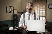 stock photo of 1950s  - Cheerful businessman showing a blank sign and smiling 1950s office on background - JPG
