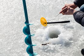 picture of winter sport  - Winter fishing. Ice fishing. Fisherman on ice fishing from the well, a special winter fishing rod. Fishing in winter. Active, cold, fish, winter fishing tackle. Sport winter fishing/