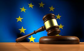 stock photo of union  - European Union law legislation and parliament concept with a 3d rendering of a gavel on a wooden desktop and the EU flag on background - JPG