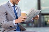 business, news, break and people and concept - close up of smiling businessman reading newspaper and poster