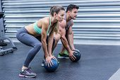 Squatting muscular couple doing ball exercise poster