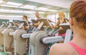 picture of elliptical  - Back view of personal woman coach looking at group of people in a elliptical trainer session on fitness center - JPG