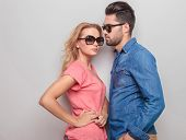 foto of she-male  - Side view of a young casual man looking at his girlfriend while she is holding her hands on her waist - JPG