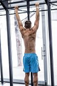 foto of pull up  - Back view of a muscular man doing pull up exercises - JPG