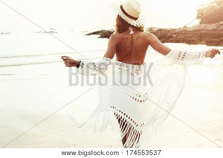 poster of Beautiful boho styled model wearing white crochet swimsuit posing on the beach in sunlight