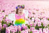 Little Girl In Fairy Costume Playing In Flower Field poster