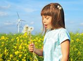 image of dynamo  - Little girl in front of windmills blowing dandelions - JPG