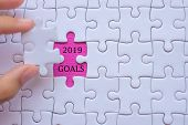 Woman Hand Holding White Jigsaw Puzzle Piece With Words 2019 Goals. Business Resolutions, Success, G poster