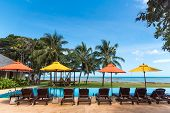 Beautiful Luxury Tropical Resort, Umbrella And Relaxing Rattan Chairs Beside The Swimming Pool Aroun poster