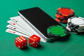 Mobile Phone Casino Online. Mobile Phone And Game Cards With Chips And Dice On A Green Gaming Table. poster