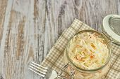 One Jar Of Sauerkraut And Carrots In Its Own Juice With Spices On A Light, White Wooden Table, Top V poster