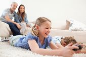 Children playing video games with their parents on the background in a living room