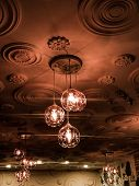 Lighting From The Ceiling. Chandeliers And Old Ceiling.   Beautiful Lighting. poster