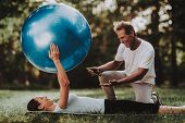 Young Couple In Sportswear Doing Yoga In Park. Sport And Healthcare Concept. Young Man Outdoor. Summ poster