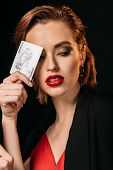 Portrait Of Attractive Girl In Red Dress And Black Jacket Holding Joker Card Isolated On Black poster