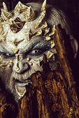Evil Goblin With Horns On Head. Druid Behind Old Bark On Black Background. Monster With Sharp Thorns poster