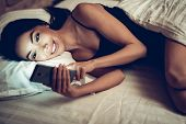 Girl Using Smartphone On Bed Before Sleeping. Mobile Addict Concept. Happy Woman Holding Mobile Phon poster