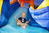 picture of yellow castle  - Boy sliding down an inflatable Side - JPG