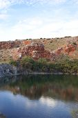 stock photo of bottomless  - Red rocks and cliffs by a small lake at the Bottomless Lakes State Park in Southeast New Mexico - JPG