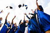 stock photo of toga  - Image of happy young graduates throwing hats in the air - JPG