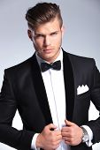 image of hunk  - cutout picture of an elegant young fashion man holding both hands on his tuxedo jacket while looking at the camera - JPG