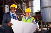 pic of machinery  - industrial engineers standing in front of a large oil refinery machinery with blueprint on hand - JPG