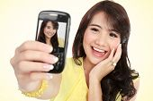 picture of handphone  - Happy young girl take the picture her self with handphone - JPG