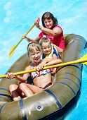 foto of inflatable slide  - Family with children  ride  rubber boat at  swimming pool  - JPG