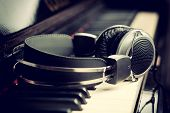 stock photo of harmony  - Piano keyboard with headphones for music  with studio lighting - JPG