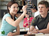 stock photo of classmates  - Happy teenage students examining DNA model and taking notes in science class - JPG