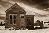 stock photo of shacks  - Old small building in ghost town in sepia tone.