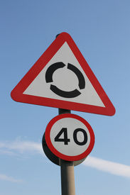 picture of mph  - Metal UK roundabout warning sign and 40 mph speed limit reminder on pole against blue sky - JPG