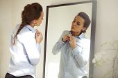 image of up-skirt  - Attractive young woman in front of mirror buttoning up her shirt - JPG