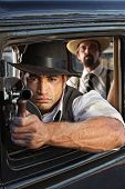 stock photo of tommy-gun  - 1920s vintage gangsters shooting submachine gun from car