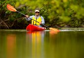 stock photo of canoe boat man  - young man in red kayak in tropical destination - JPG