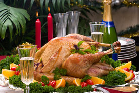 image of christmas dinner  - Garnished roasted turkey on Christmas decorated table with candles and flutes of champagne - JPG