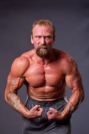 pic of body builder  - Middle aged Caucasian body builder man flexing muscles showing torso pecs biceps and veins isolated - JPG