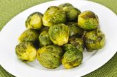 picture of brussels sprouts  - Plate of roasted green brussels sprouts on placemat - JPG
