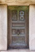 pic of burial-vault  - Front view of weathered mausoleum door in cemetery - JPG