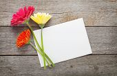 stock photo of gerbera daisy  - Three colorful gerbera flowers and blank greeting card on wooden table - JPG