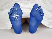 foto of unnatural  - Body under a white sheet suicide sleeping murder or natural death NATO symbol - JPG