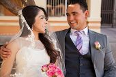 stock photo of boutonniere  - Young Hispanic couple looking at each other and smiling on their wedding day - JPG