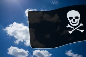 foto of skull crossbones flag  - Pirate Black Flag with white Skull and Crossbones sign on blue sky background - JPG