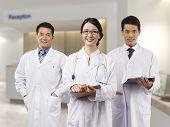 picture of hospital gown  - asian medical team standing in hospital lobby - JPG