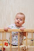 foto of bassinet  - beautiful baby with big blue eyes in a cot - JPG