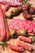 image of antipasto  - Salami antipasto and green olives on olive board