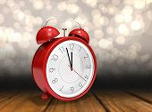 foto of count down  - Alarm clock counting down to twelve against shimmering light design over boards - JPG